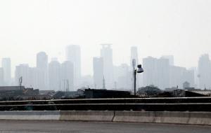 Terlihat kabut sore jam 15.00 Wib dari jembatan fly ofer terminal Kampung Melayu, Jakarta, Minggu (25/10/2015). Badan Meteorologi dan Geofisikan (BMKG) menyatakan langit Ibukota yang berkabut bukan karena efek dari pembakaran lahan yang terjadi di Sumatera dan Kalimantan, melainkan karena saat ini sedang terjadi cuaca haze yaitu kondisi kekaburan udara.