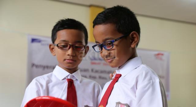 Egra (kiri) dan Egri (kanan), murid kelas 6 SDN 007 Ranai Bunguran Timur sedang mencoba rangka kacamata setelah diperiksa matanya pada acara Penyerahan 2.000 Kacamata Anak-anak Kabupaten Natuna di SDN 007 Ranai Bunguran Timur, Kabupaten Natuna, Kepulauan Riau, Rabu (11/1). AKTUAL/Humas Astra