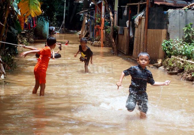 Sejumlah anak-anak bermain banjir yang berada di kampung Bayur di RW 04 Cipinang Melayu, Jakarta Timur, Minggu (26/2/2017), kembali terendam banjir. Air yang menggenangi kawasan tersebut setinggi lebih dari 30 centimeter, diduga akibat dari kali sunter . Namun sejumlah anak-anak terlihat senang memanfaatkan banjir untuk bermain air. AKTUAL/Munzir