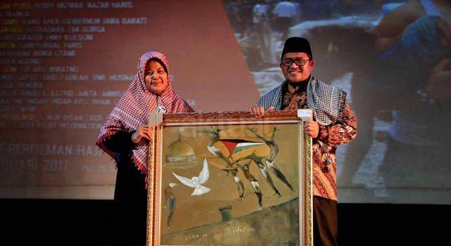 Dewan Syuro PUI sekaligus Gubernur Jawa Barat Ahmad Heryawan (kanan) menerima lukisan bertema Palestina dan Kemanusiaan dari Ketua Adara Relief Nurjanah Hulwani (kiri) di acara TERJEBAK, di Gedung Pusat Perfilman Usmar Ismail, Kuningan, Jakarta Selatan, Kamis (16/2/2017) malam. AKTUAL/HO