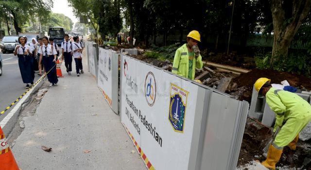 Pelajar melintas di tengah pembongkar trotoar untuk pembangunan penataan pedestrian di Jalan Perwira, Jakarta Pusat, Senin (17/7). Pemprov DKI tengah melakukan penataan jalur pedestrian yang bertujuan untuk memberikan kenyamanan dan keamanan kepada pejalan kaki. AKTUAL/Tino Oktaviano