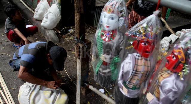 Perajin Ondel-ondel menyelesaikan pembuatan boneka khas Betawi di 'Kampung Ondel-ondel' Kramat Pulo, Jakarta, Senin (17/7/2017). Warga di permukiman padat penduduk ini banyak yang menggantungkan mata pencarian dengan membuat ondel-ondel ataupun mengamen dengan ondel-ondel. AKTUAL/Munzir