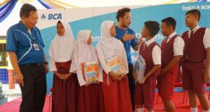 Direktur BCA Santoso (kiri) dan Musisi Nidji, Giring Ganesha (kanan), berdialog dengan siswa SD Negeri 7 Gadingrejo, usai menyerahkan donasi buku melalui program Gerakan Berbagi Buku untuk Indonesia, di Bandar Lampung, Lampung, Jumat (21/7). BCA mengumpulkan dana dari nasabah Rp1,05 miliar yang kemudian diwujudkan dalam bentuk buku yang didonasikan ke 104 sekolah penerima di 60 titik di Indonesia