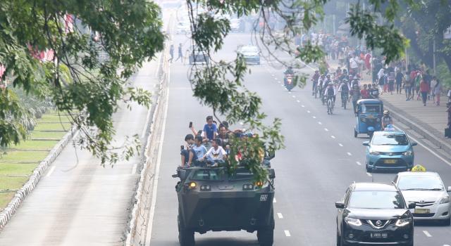 Warga memanfaatkan memontum menaiki dan berkeliling dengan Anoa dikawasan Monumen Nasional, Jakarta Pusat, Minggu (13/8). Kemenhan mengadakan Pameran produk alat utama sistem pertahanan (alutsista) dan mengajak warga mencoba kendaraan jenis komodo yang belum pernah digunakan, tapi sering diikutsertakan dalam uji ketangkasan.Produk dalam negeri buatanPT Pindad ini kendaraan tempur antipeluru yang dibanggakan Indonesia. AKTUAL/Tino Oktaviano