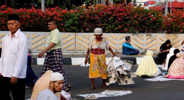 Pemulung mengais sampah koran yang ditinggalkan jemaah usai salat id Idul Adha di kawasan pasar Senen, Jakarta, Jumat (1/9/2017). Usai solat Idul Adha, koran yang digunakan sebagai alas ditinggalkan begitu saja sehingga mengotori jalanan. AKTUAL/Munzir