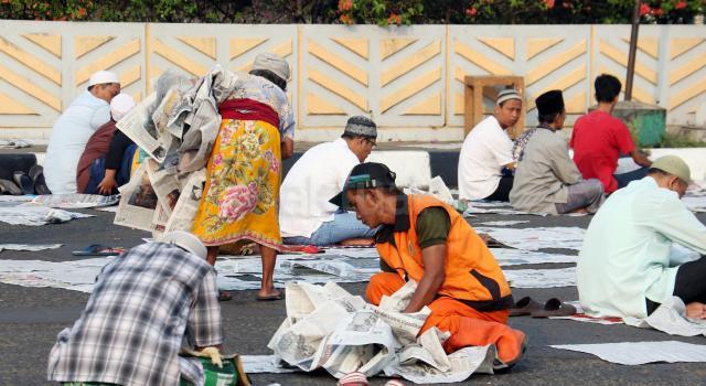Seorang petugas kebersihan mengumpulkan sampah koran yang ditinggalkan jemaah usai salat id Idul Adha di kawasan pasar Senen, Jakarta, Jumat (1/9/2017). Usai solat Idul Adha, koran yang digunakan sebagai alas ditinggalkan begitu saja sehingga mengotori jalanan. AKTUAL/Munzir