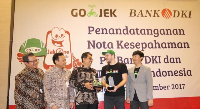 Direktur Bisnis Bank DKI,Antonius Widodo Mulyono (tengah) menerima plakat dari Chief Marketing Officer Gojek Indonesia, Piotr Jakubowski (2 kanan) disaksikan Direktur Teknologi & Operasional Bank DKI, Priagung Suprapto (2 kiri),VP Grup Pengembangan Dana & Jasa Bank DKI, Diki Jatnika (paling kiri) dan GoPay Strategic Partnership Head, Vincent (paling kanan) usai penandatanganan MoU Bank DKI dan Gojek Indonesia di Jakarta, Selasa (7/11). Kerjasama tersebut mencakup interoperabilitas uang elektronik, interkoneksi ekosistem pembayaran dan perluasan channel pembayaran pajak dan retribusi. AKTUAL/Eko S Hilman