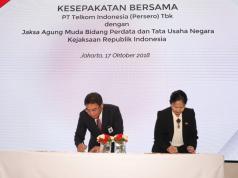 """Direktur Utama Telkom Alex J Sinaga (kiri) bersama Jamdatun Loeke Larasati Agoestina (kanan) menandatangani Kesepakatan Bersama tentang Penanganan Masalah Hukum Bidang Perdata dan Tata Usaha Negara di Jakarta (17/10). Kerjasama ini merupakan upaya Telkom untuk memperkuat penerapan Good Corporate Governance (GCG) dalam menunjang kinerja perusahaan dan mewujudkan visi """"Be the King of Digital in the Region""""."""