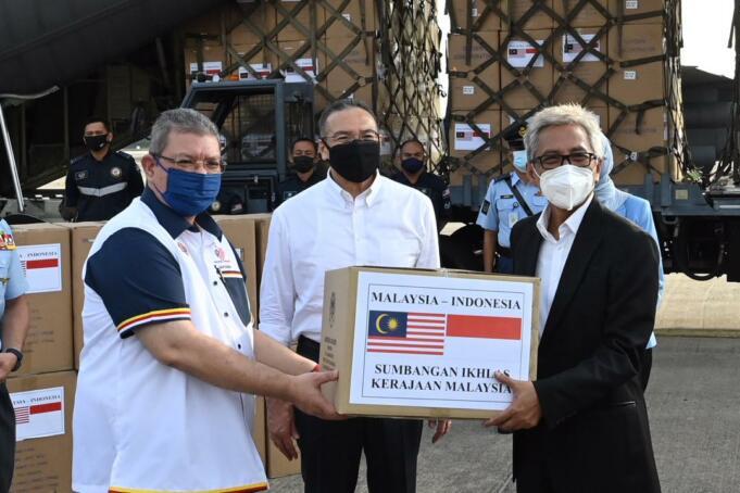 Menteri Luar Negeri Malaysia Saifuddin Abdullah (kiri) dan Menteri Pertahanan Malaysia Hishamuddin Hussein (tengah) saat menyerahkan bantuan kepada Duta Besar RI di Kuala Lumpur, Hermono.
