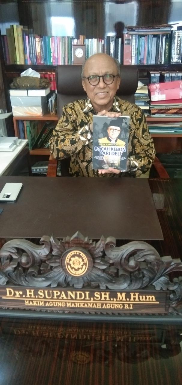 Prof. Dr. Supandi, SH, M.Hum, Ketua Muda kamar Tata Usaha Negara (TUN) di Mahkamah Agung menunjukkan buku Biografinya